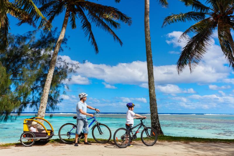 Father and kids enjoy a bike ride alongside the beautiful beaches of Rarotonga
